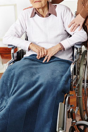 Elderly woman in a wheelchair being cared for at a nursing home