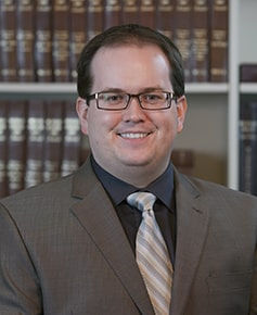 Young male attorney with dark hair and glasses in a brown suit and tie standing in front of a bookshelf