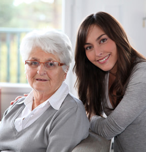 Young brunette woman standing up and caring for her elderly grandmother who's sitting down