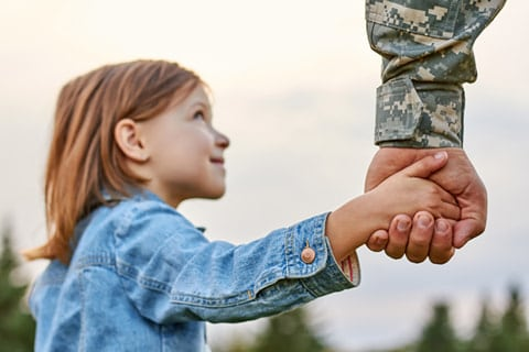 Picture of the hand of a soldier in a military uniform holding the hand of his daughter