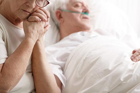 Woman caring for elderly man in bed and talking about Michigan elder law