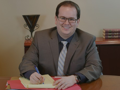 Estate planning attorney Sean Nichols wearing a brown suit and glasses while sitting at his desk writing on a notepad