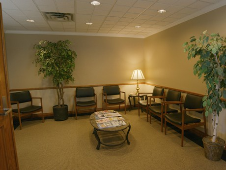 The waiting room inside the law firm of Sean J Nichols, PLLC the room is dimly lit with decorative plants to provide a soothing environment and there's plenty of cushioned chairs for clients to sit.