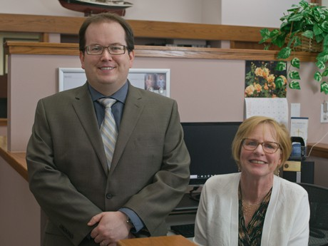 Elder law and probate lawyer Sean Nichols wearing a brown suit and glasses while standing next to his administrative assistant who is wearing a white shirt and glasses