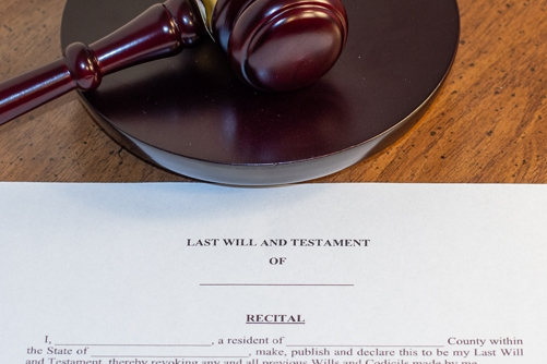 A Michigan Last Will and Testament laying on a desk with a judges gavel above it symbolizing estate litigation for wills