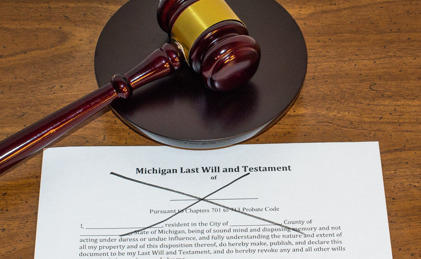 Judges gavel next to a Michigan will that is crossed off symbolizing probate without a will