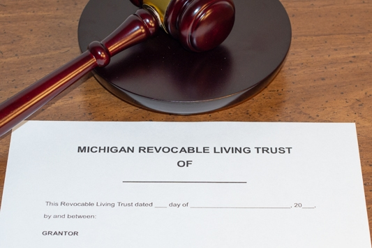Michigan revocable living trust on a desk underneath a gavel symbolizing probate and trust litigation