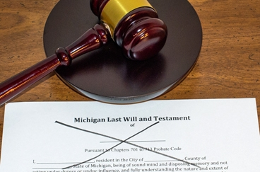 Michigan last will and testament on a desk crossed out in black marker symbolizing probate without a will