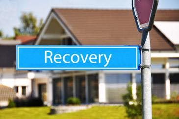 Blue sign with the word recovery on it next to a house symbolizing estate recovery